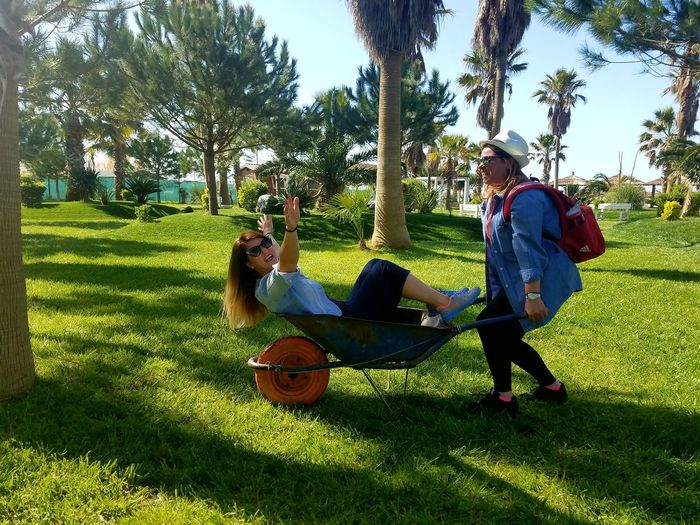 Woman Enjoying While Sitting In Wheelbarrow Pulled By Friend