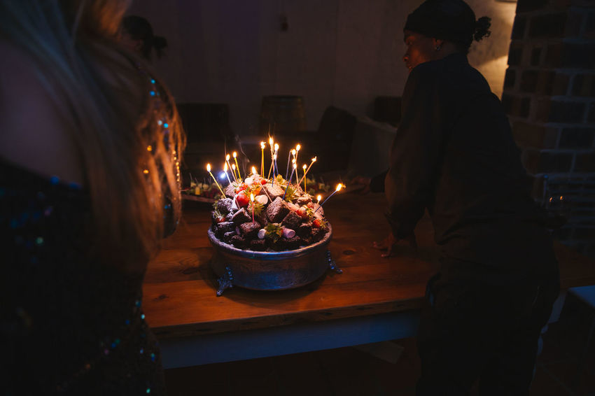 Birthday Cake Adult Belief Birthday Burning Candle Celebration Chocolate Cake Fire Fire - Natural Phenomenon Flame Food Food And Drink Glowing Heat - Temperature Illuminated Indoors  Lifestyles Men Real People Rear View Table Women