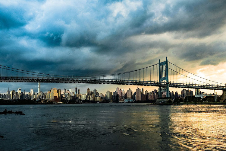 View of suspension bridge over river against cloudy sky
