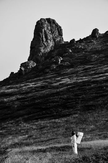 Rear view of woman on rock against sky
