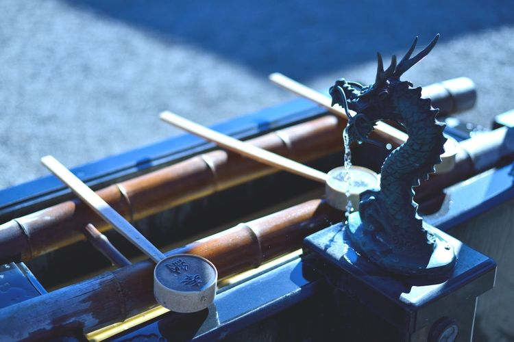 High angle view of wooden spoons by dragon drinking fountain at shinto shrine