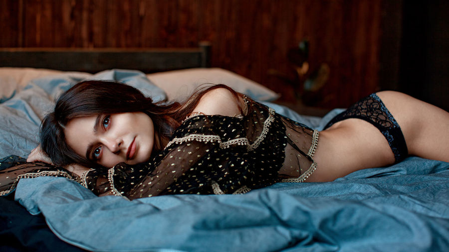 Portrait of sensuous young model wearing lingerie while lying on bed at home
