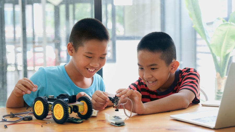 Brothers making toy car on table at home