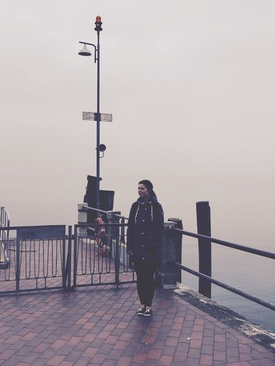 Woman standing by railing against sea in foggy weather
