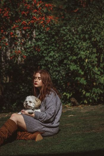 Young woman holding dog while sitting on grassy field against trees
