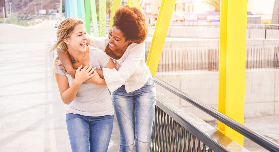 Young multiracial friends having fun together outdoor Togetherness Two People Women Emotion Happiness Young Women Young Adult Smiling Lifestyles Leisure Activity Love Bonding Positive Emotion Casual Clothing Real People Friendship