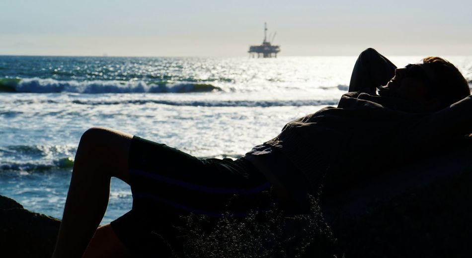 Man lying on rock at sea shore against sky