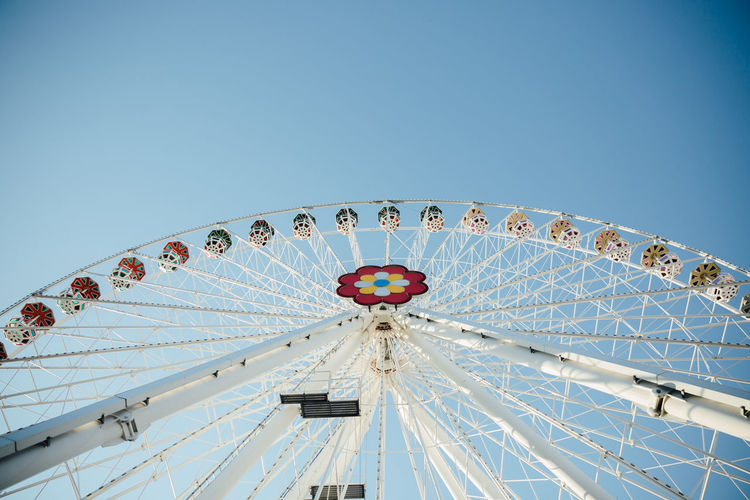 White Ferris wheel from low angle view Symmetry Amusement Park Amusement Park Ride Arts Culture And Entertainment Big Wheel Blue Blue Sky Carousel Clear Sky Day Ferris Wheel Leisure Activity Low Angle View No People Outdoors Sky Traveling Carnival White