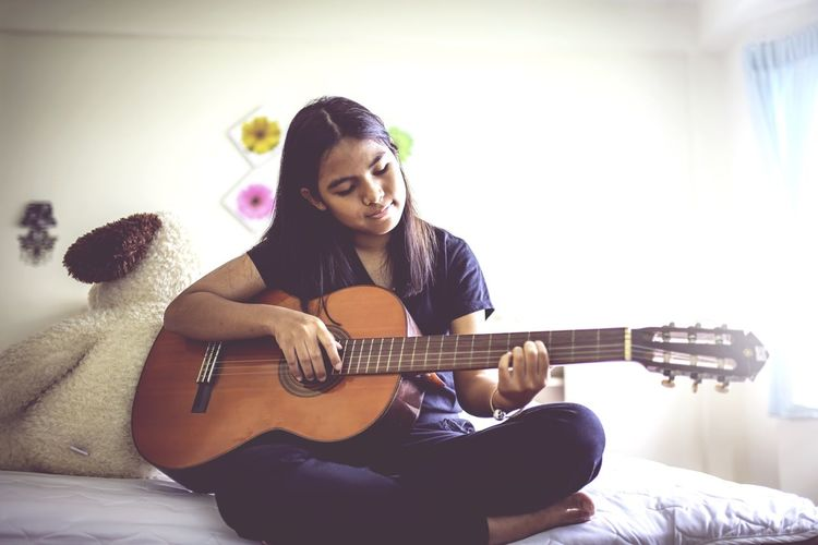 Teenage Girl Playing Guitar On Bed