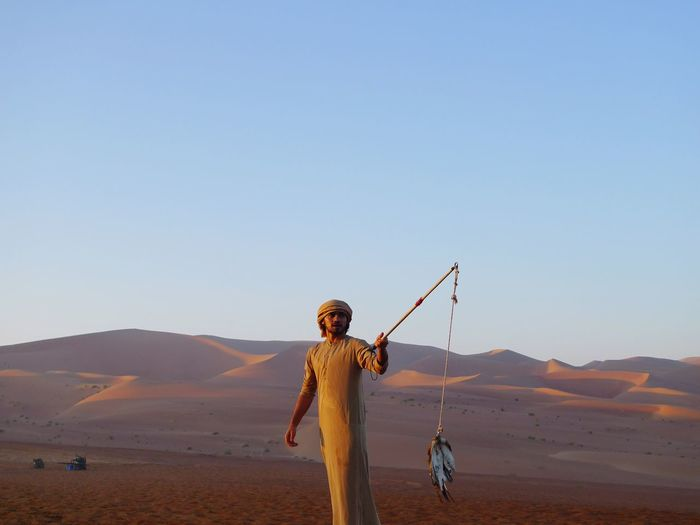Desert sunrise Rub Al Khali Falconry Falconer Desert Clear Sky One Person Standing Copy Space Outdoors Real People Beauty In Nature Sand Dune