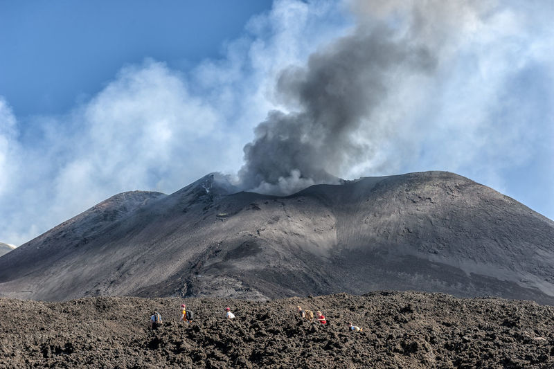 Smoke emitting from volcanic mountain against sky