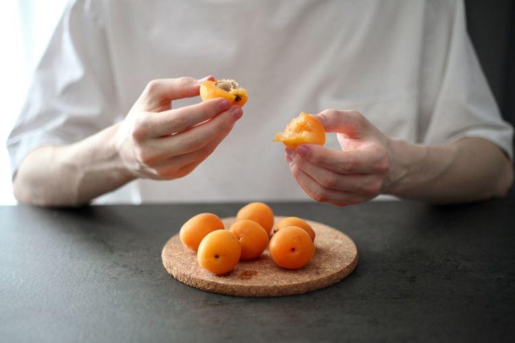 Cropped image of man holding orange fruits