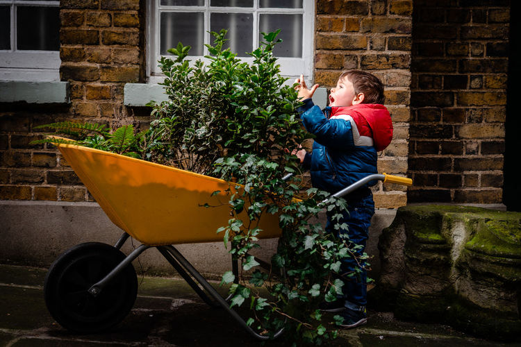 Side view of boy holding umbrella against plants