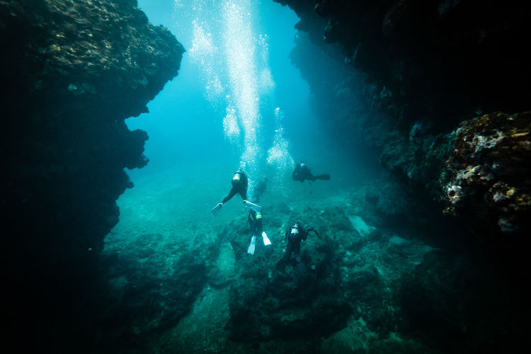 High Angle View Of People Scuba Diving Amidst Rock Formations In Sea At Ishigaki