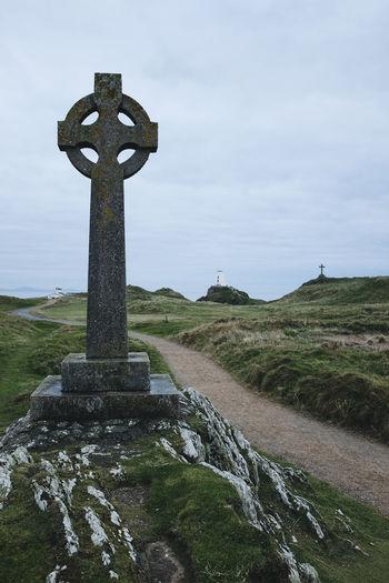 Cross on field against sky