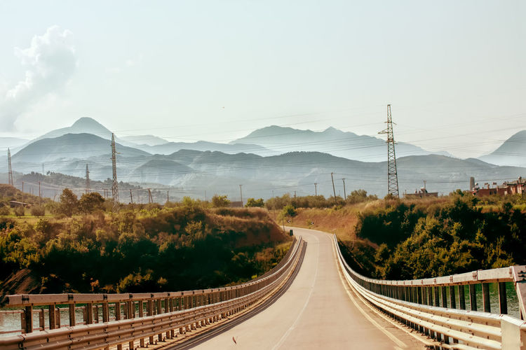 Panoramic view of road leading towards mountains against sky