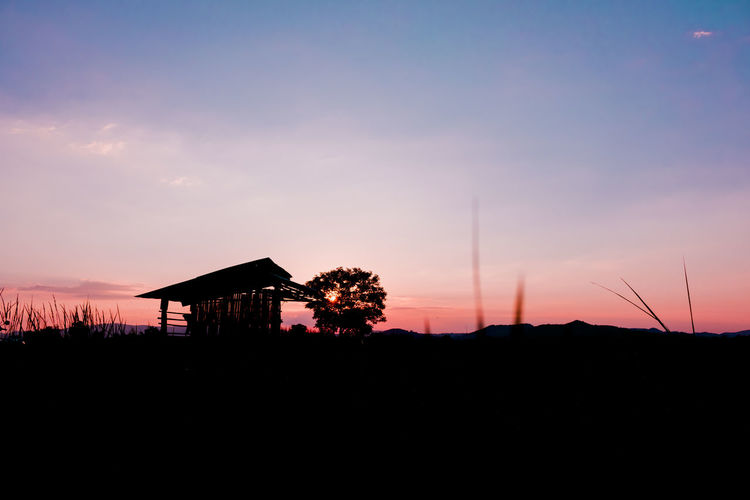 Silhouette built structures against sky during sunset