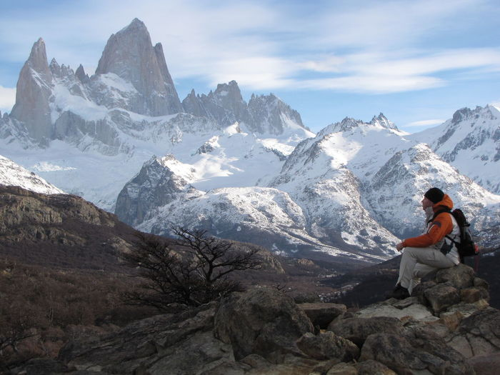 Man Sitting On Rock Against Snowcapped Mountains