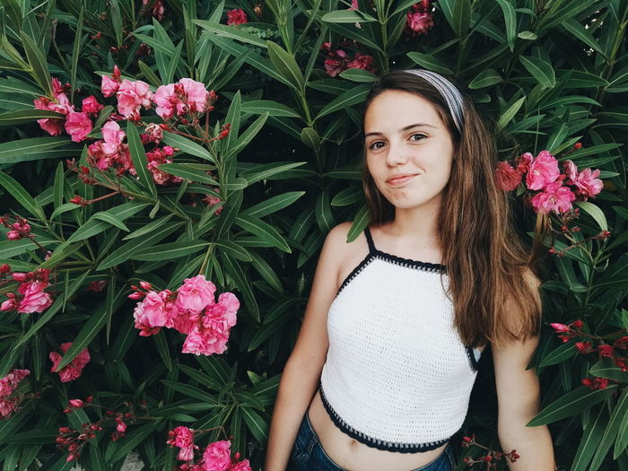 Portrait Of Teenage Girl Standing Amidst Pink Flowers Blooming Outdoors
