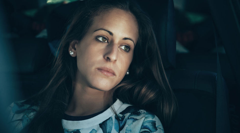 Portrait of sad young woman girl sitting inside of car crying with a tear in her face Friends Fun Horizontal Nature Passenger Travel Trip Woman Caucasian Cheerful Crazy Crying Friendship Girl Inside Leisure Lifestyles One Person Real People Roadtrip Sad Sadness Tear Togheter Vehicle Interior