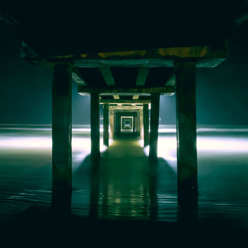 Angles Architectural Column Architecture Beach Bridge - Man Made Structure Built Structure Glow Green Illuminated Infinity Night No People Ocean Peaceful Pier Seaside Solace Underside Vacation Vanishing Point Water