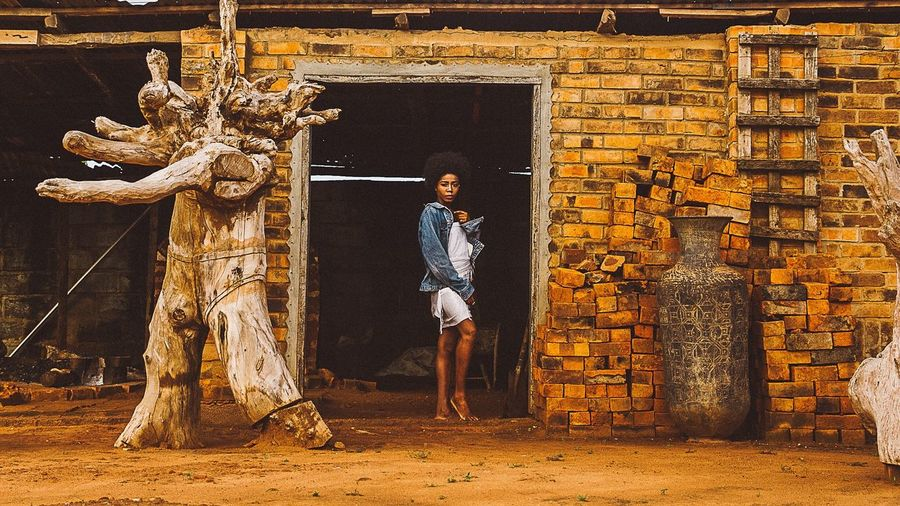 Portrait of young woman standing at doorway of abandoned building