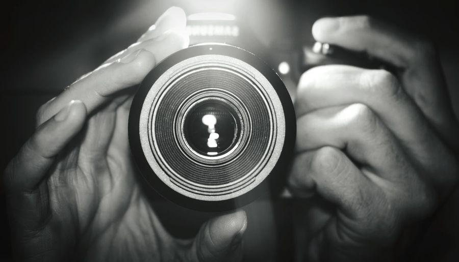 Cropped hands adjusting lens of camera