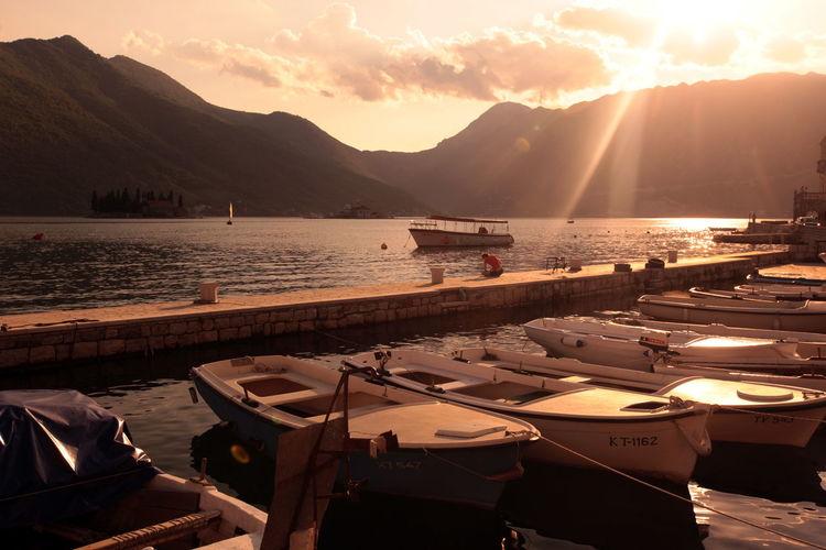 Boats moored at harbor at sunrise