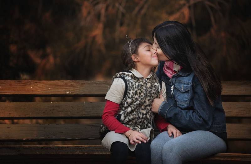 Bench Sitting Women Seat Togetherness Females Childhood Real People Child Two People Girls Leisure Activity Casual Clothing Three Quarter Length Emotion Adult Focus On Foreground Wood - Material Positive Emotion Park Bench Warm Clothing Daughter Outdoors