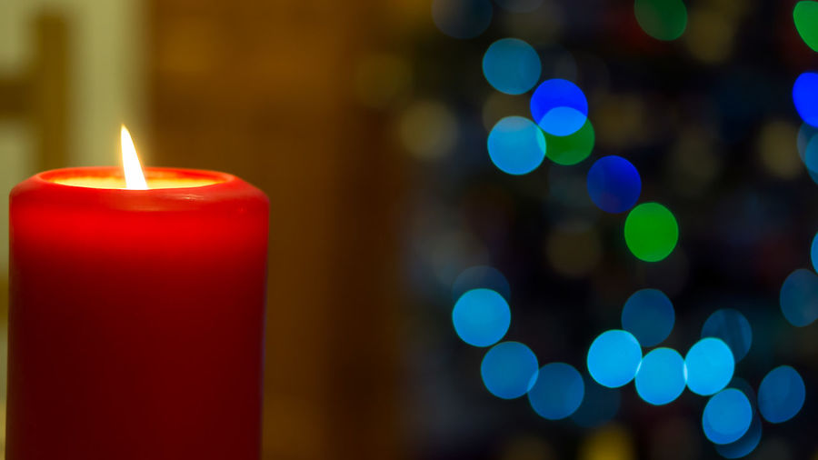 Close-up of illuminated candles against blurred background