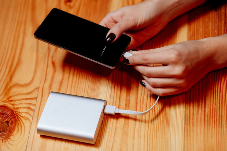 charging phone with powerbank. woman using powerbank when battery low. Power PowerbankCable Battery Charge Charger Holding Human Body Part Human Hand Low Battery Mobile Phone One Person Portable Information Device Powerbank Real People Smart Phone Technology Touch Screen Wireless Technology Women