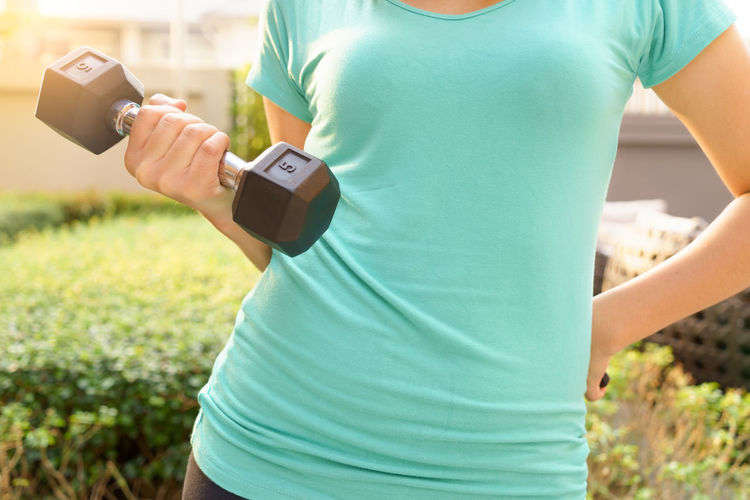 Midsection of woman exercising at park