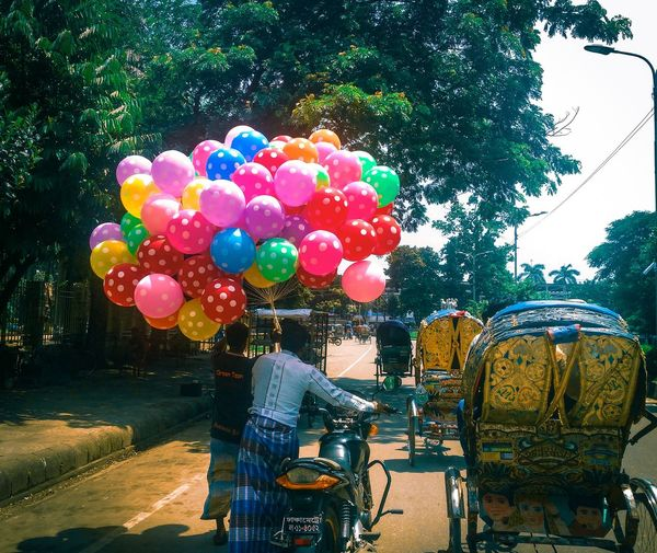 Colorful ballon seller and traditional rickshaw Tree City Balloon Multi Colored Women Street Sky Bicycle City Street Riding Bunch Blooming Clown