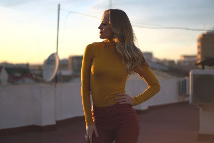 Woman standing against buildings in city during sunset