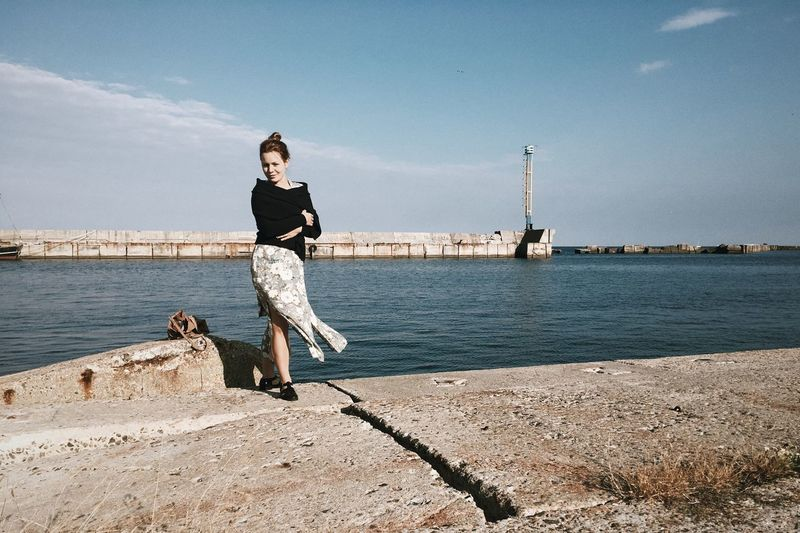 Portrait of woman standing by harbor against sky