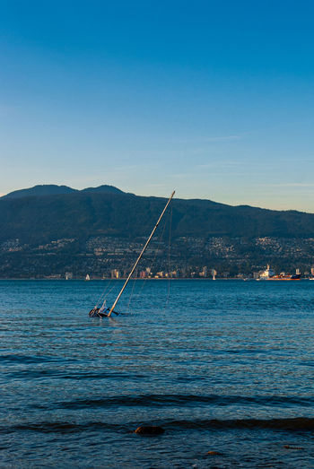 Sailboat drowning in sea against cityscape