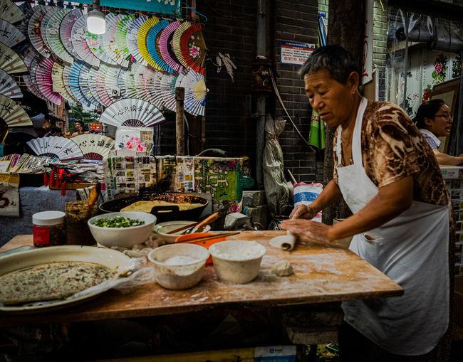 Woman preparing food at market stall