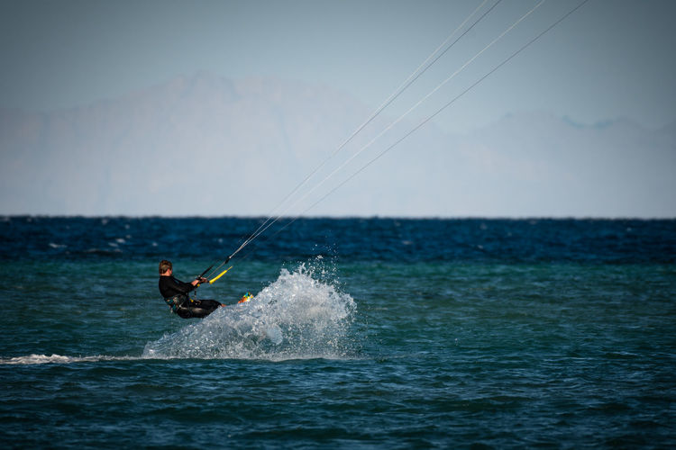Man kiteboarding over sea against sky