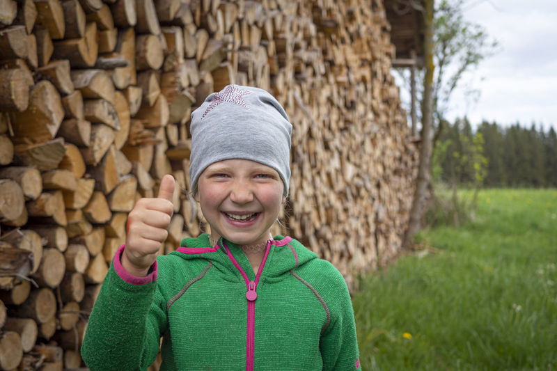 Portrait of smiling boy standing against stone wall