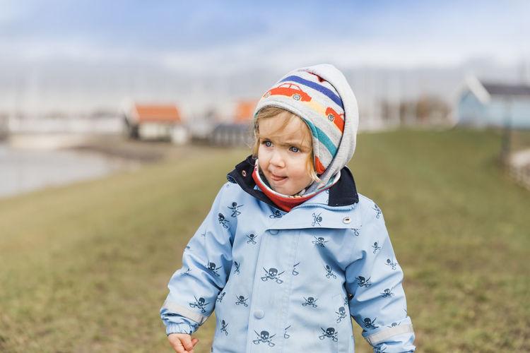 Cute Girl In Warm Clothing Walking On Field