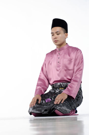 Portrait of young and handsome asian man with traditional clothing during hari raya over white background One Person Front View Studio Shot Indoors  White Background Clothing Copy Space Young Adult Sitting Full Length Young Men Three Quarter Length Cut Out Looking Away Real People Looking Casual Clothing Contemplation