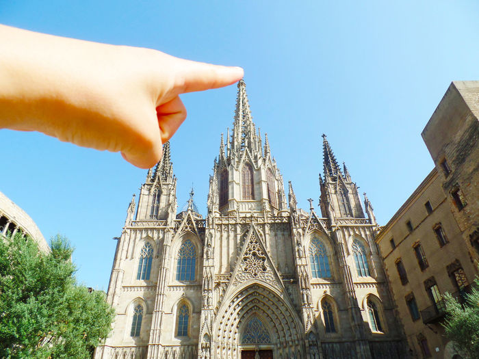 Optical illusion of person touching barcelona cathedral against clear sky