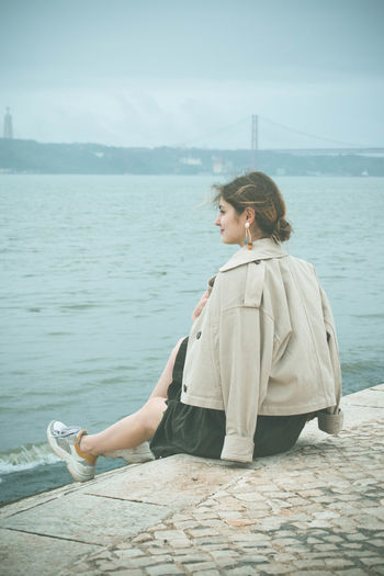 Water One Person Real People Leisure Activity Lifestyles Sea Sky Nature Sitting Young Adult Beauty In Nature Day Casual Clothing Relaxation Full Length Non-urban Scene Scenics - Nature Adult Contemplation Looking At View Outdoors Hairstyle