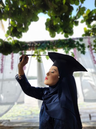 Side view of woman wearing graduation gown standing outdoors