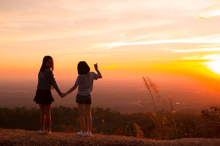 Rear view of women holding hands while standing against sky during sunset