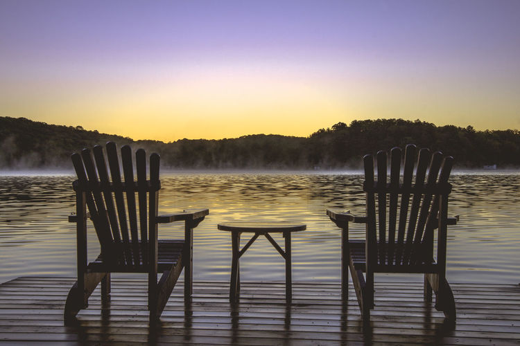 Chairs by lake against clear sky during sunset