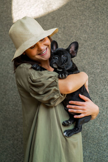Mid section of woman with dog wearing hat