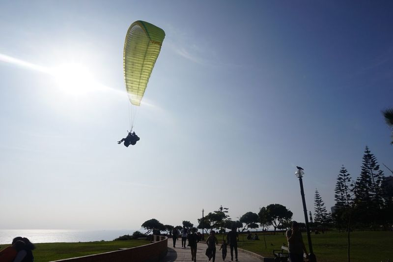 Parachute Flying Real People Leisure Activity Adventure Mid-air Lifestyles Sky Extreme Sports Low Angle View Paragliding Outdoors Sport Nature Large Group Of People Clear Sky Tree Day Men People EyeEmNewHere