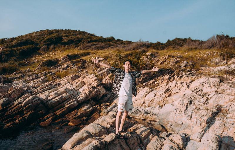 Full length of man with arms outstretched standing on rock