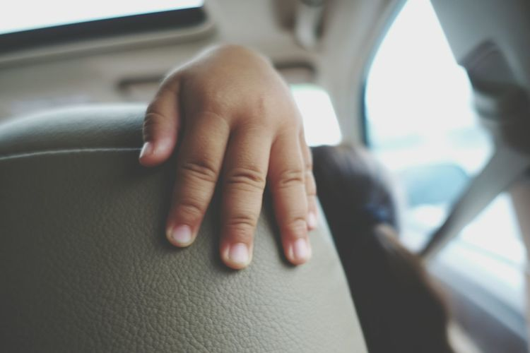 Cropped hand on car seat